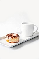 A doughnut with icing sugar and chocolate sprinkles and a cup