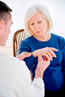 Doctor examining the wrist of elderly woman.