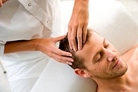 Man receiving a face acupressure massage : the pressure on acupuncture points stimulates enregy flow and releives stress.