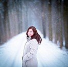 Winter portrait of a young woman outdoors on a lovely forest path