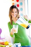 Woman making fruit smoothie in blender.