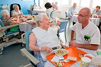 Medico_psychological assistant helping an alzheimer´s disease person to learn again gestures to eat independently with an adapted spoon. Residential h...