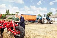 Farmers adjusting machinery in field