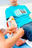 Nurse taking teenager blood sample. Limoges hospital, France.