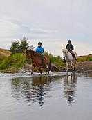 Boys riding horses through creek