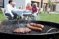 Germany, Bavaria, Nuremberg, Close up of barbecue, family sitting in background