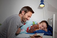 Germany, Berlin, Father reading book while son sleeping (thumbnail)