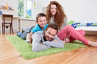 Germany, Berlin, Family lying on floor, smiling, portrait (thumbnail)