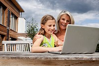 Germany, Bavaria, Nuremberg, Grandmother and granddaughter using laptop