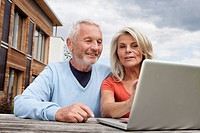 Germany, Bavaria, Nuremberg, Senior couple using laptop