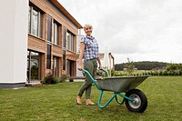 Germany, Bavaria, Nuremberg, Mature woman with wheelbarrow in garden (thumbnail)