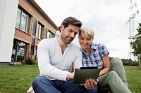 Germany, Bavaria, Nuremberg, Mature couple using digital tablet in garden