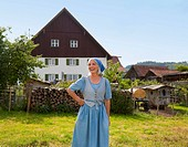 Germany, Bavaria, Mature woman standing in front of farm
