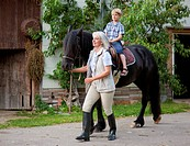 Germany, Bavaria, Mature woman leading boy on horse