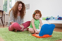 Germany, Berlin, Mother and daughter using laptop on floor