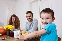 Germany, Berlin, Family having breakfast, smiling, portrait