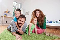 Germany, Berlin, Family sitting on floor, smiling, portrait
