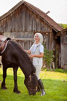 Germany, Bavaria, Mature woman with horse