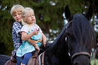Germany, Bavaria, Boy and girl riding horse