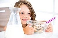 Germany, Girl eating muesli in kitchen (thumbnail)