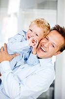 Germany, Father carrying son, smiling, portrait