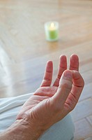 Close view of man's hand practising yoga, sitting in the lotus position