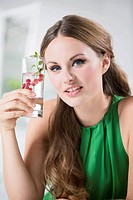 Germany, Young woman holding glass of water with berries