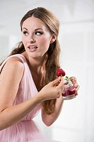 Germany, Young woman holding strawberry in her hand