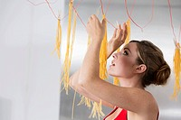 Germany, Young woman hanging up pasta to dry