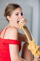 Germany, Young woman eating pastry, close up