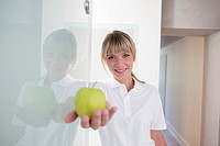 Germany, Dentist holding green apple, smiling, portrait