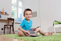 Germany, Berlin, Boy sitting on floor with book, smiling, portrait