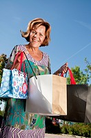 Germany, Munich, Senior woman holding shopping bag, smiling, portrait