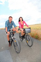 Couple riding bicycle on country road