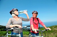 Senior couple drinking water during bike ride