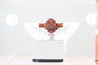 Businessman relaxing in office in front of laptop computer