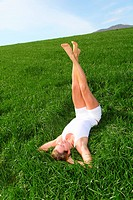 Woman laying down green field with legs up