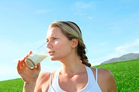 Beautiful blond woman drinking milk in countryside