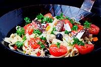 frische Tagliatelle mit Tomaten und Oliven in einer Pfanne