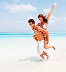 Image of happy young couple enjoying piggy back ride together on beach