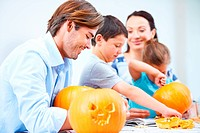 A young family carving Halloween decorations together