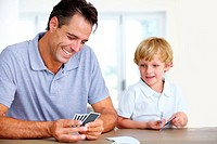 Dad and son playing a friendly game of ´go fish´ together while son sneaks a peek at his father´s cards