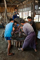 Myanmar, Burma  Three Young Men Hammer Red-hot Metal Just Taken from the Blacksmith's Fire, Inle Lake, Shan State