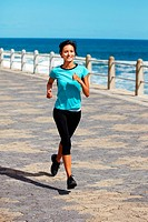 Attractive young woman running on the pier at the beach