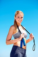 An attractive young woman smiling while holding a skipping rope over her shoulders