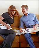 Homeowner Ellin LaVar and designer Nate Berkus browse catalog on brown couch