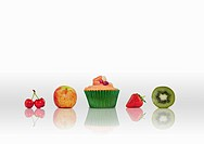 Line_up of fruits and one cup cake