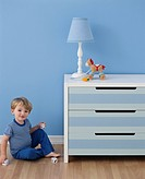 Boy Playing by Chest of Drawers