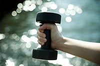 Woman lifting a dumbbell,hands close_up
