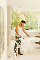 Mid adult man ironing clothes at home